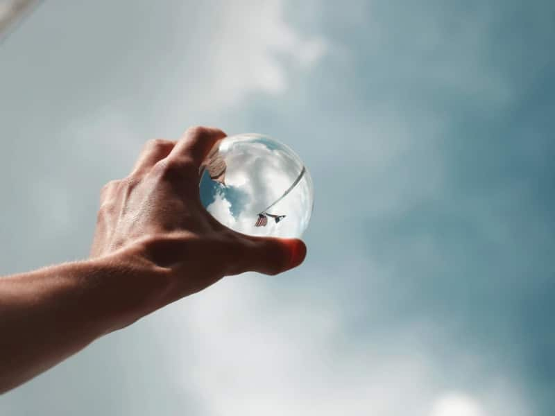 man reaching for glass ball sky